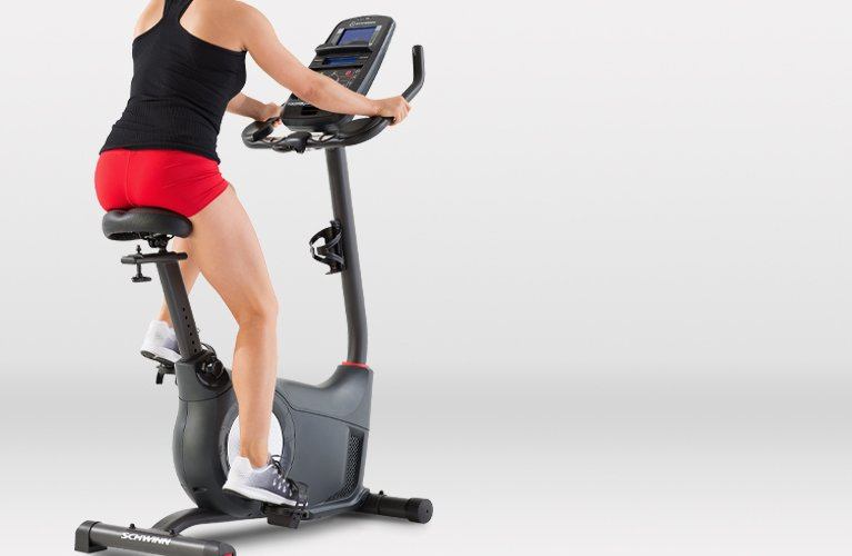 Woman riding a Schwinn upright exercise bike